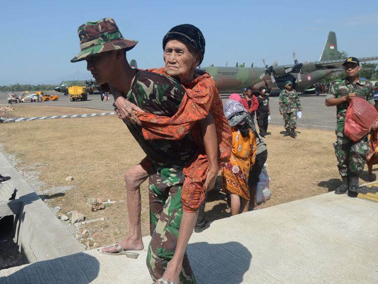 Indonesian soldiers carry an elderly woman evacuated after an earthquake and tsunami hit Palu