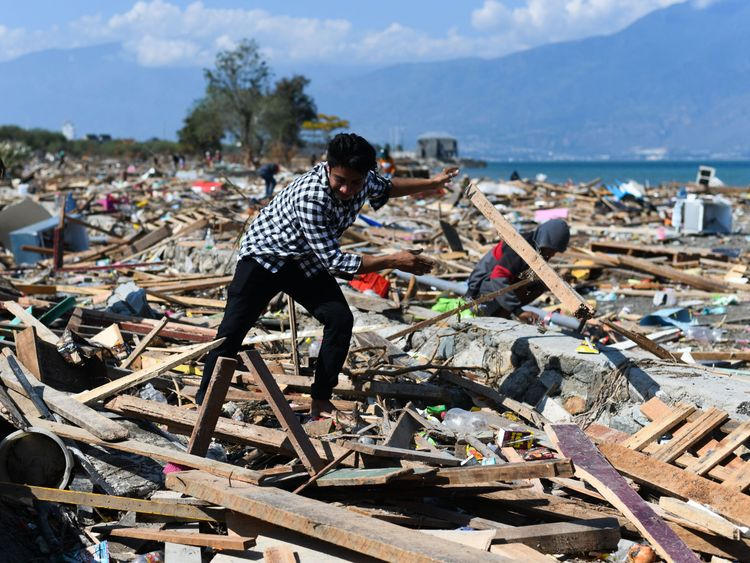 A survivor picks through debris in badly-hit Palu