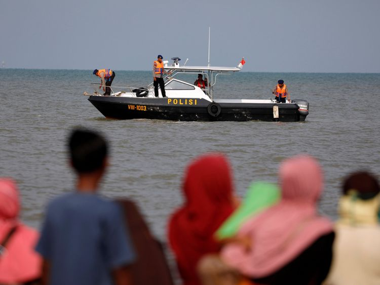 People watch rescue team members on a boat before they head to the Lion Air, flight JT610, sea crash location