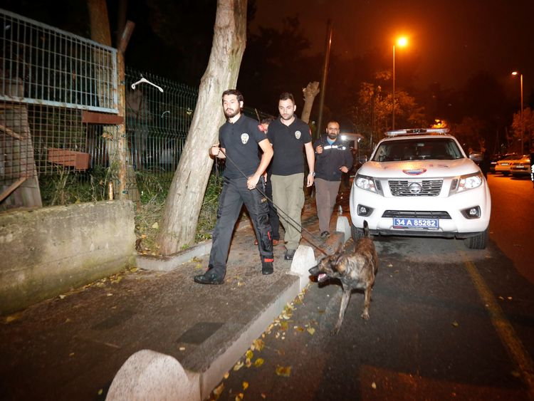 Turkish police officers and a sniffer dog examine the outside of the Saudi consul's home in Istanbul
