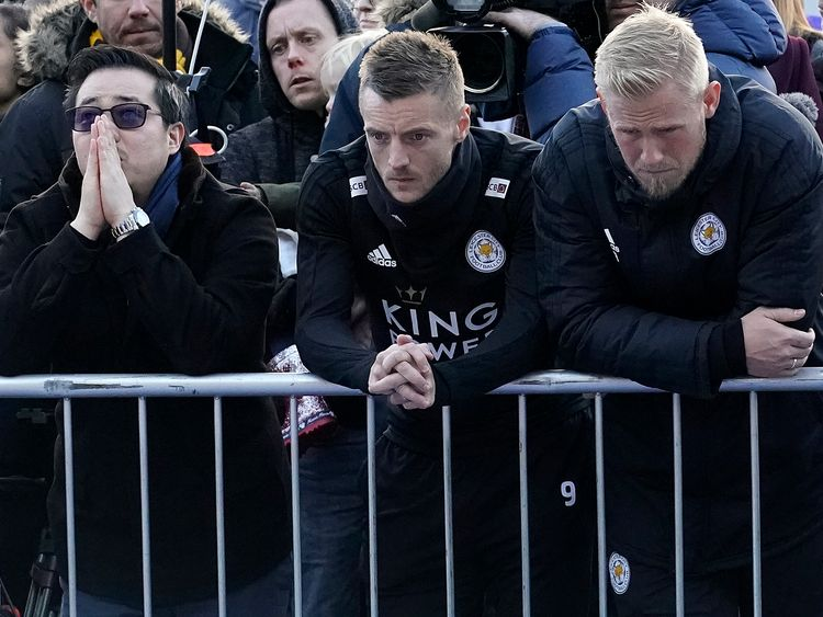 Aiyawatt Srivaddhanaprabha, the late chairman's son, stands next to Leicester players Jamie Vardy, centre, and Kasper Schmeichel, right