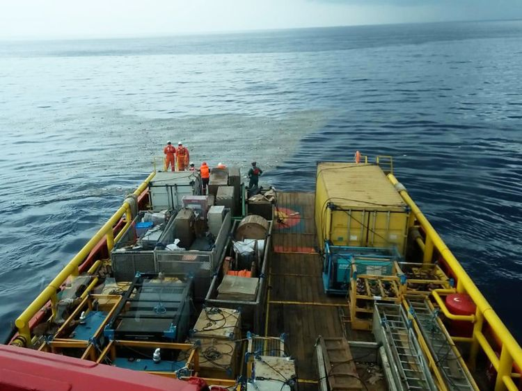 Workers on a ship look at what is believed to be debris from crashed Lion Air flight