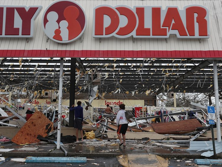 People look on at a damaged store after Hurricane Michael passed through