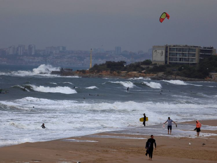 Surfers leave the sea at Carcavelos beach before hurricane Leslie arrives