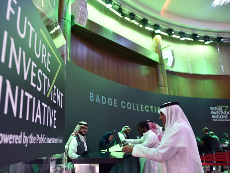 Saudi journalists collecting their press badges at the press center of the Future Investment Initiative FII