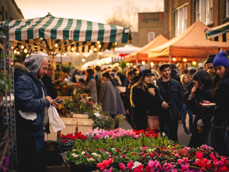 People shopping at the Columbia Road Flower Market, a Sunday street market in the London Borough of Tower Hamlets
