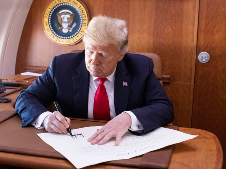 President Trump signs the commission appointing Judge Kavanaugh to the Supreme Court while on board Air Force One