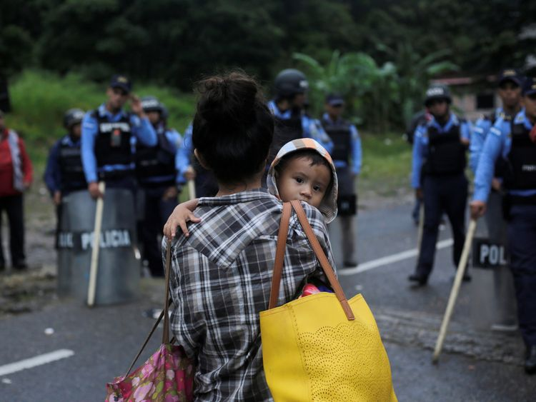 Honduran police officers stand as an Honduran migrant looks on while hoping to cross into Guatemala and join a caravan trying to reach the US