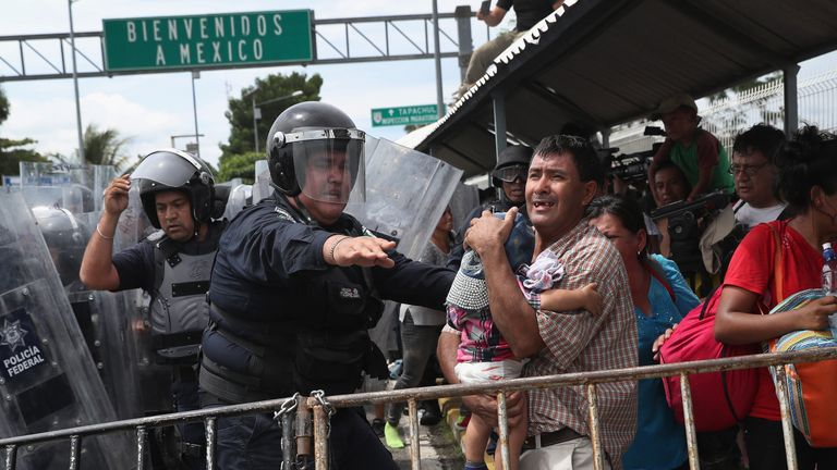 A Mexican riot policeman ushers a father and child away from a clash between migrants and officers