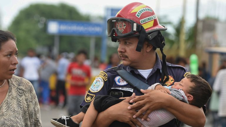A Guatemalan firefighter carries a child
