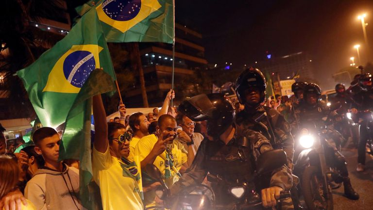 Police ride past supporters of Mr Bolsonaro in Rio de Janeiro hours before his success was revealed
