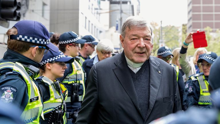 Vatican Treasurer Cardinal George Pell is surrounded by Australian police as he leaves the Melbourne Magistrates Court