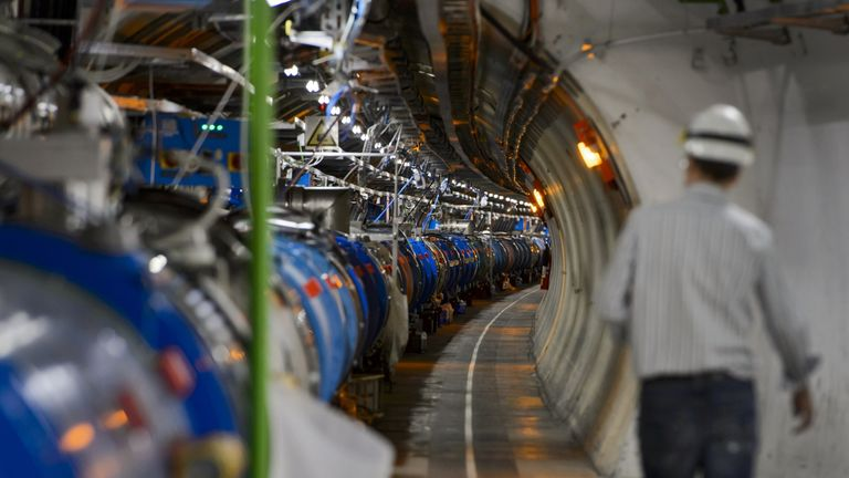 A scientist walks in a tunnel inside the European Organisation for Nuclear Research (CERN) Large Hadron Collider (LHC), during maintenance works on July 19, 2013 in Meyrin