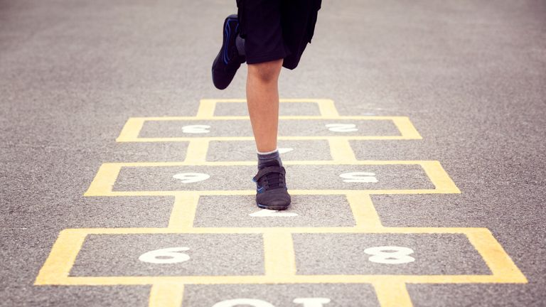 Child playing hopscotch on school playground