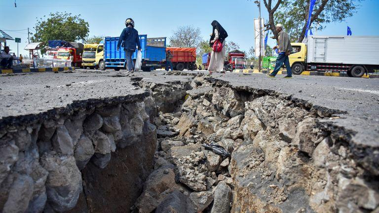 People walk near a road damaged by an earthquake at Kayangan Port in Lombok in August. Pic: Antara Foto/Ahmad Subaidi
