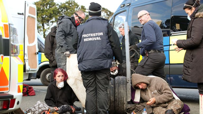 Police had to cut two people free after they apparently cemented their arms into stacks of tyres