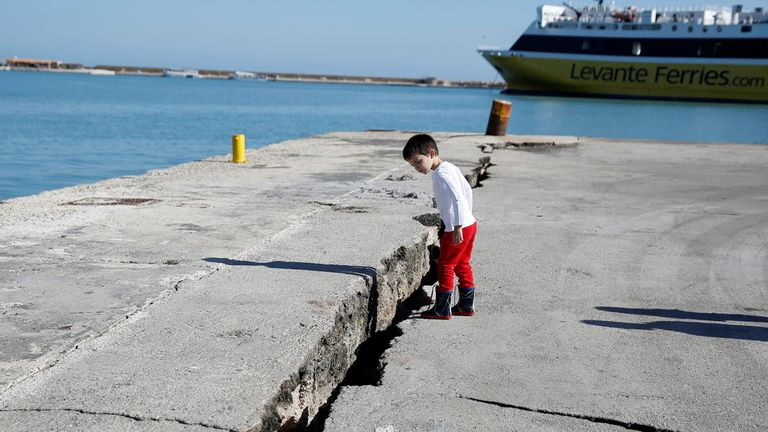 A child looks at the damaged pier of the port of Zakynthos, following an earthquake off the Zakynthos Island, Greece, October 26, 2018. REUTERS/Costas Baltas
