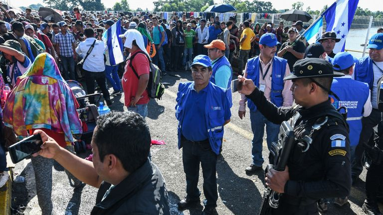 A Guatemalan policeman takes a picture as Honduran migrants travel to the US