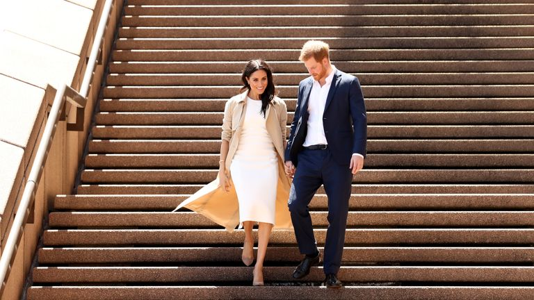 Prince Harry and his wife Meghan walk down the stairs of the iconic Opera House to meet the crowds
