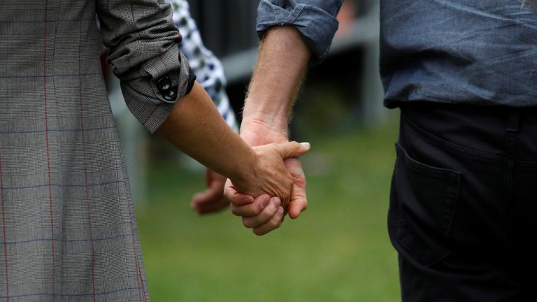 Prince Harry and Meghan, Duchess of Sussex hold hands while attending a community picnic at Victoria Park in Dubbo