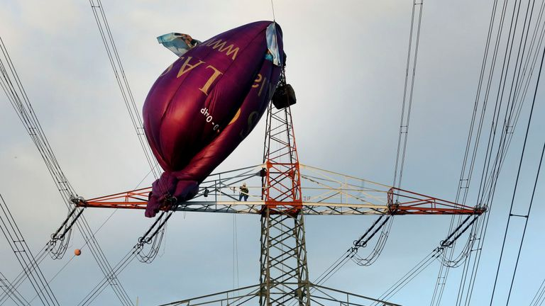 A hot air balloon sits on top of a high-voltage power line in Bottrop, Germany