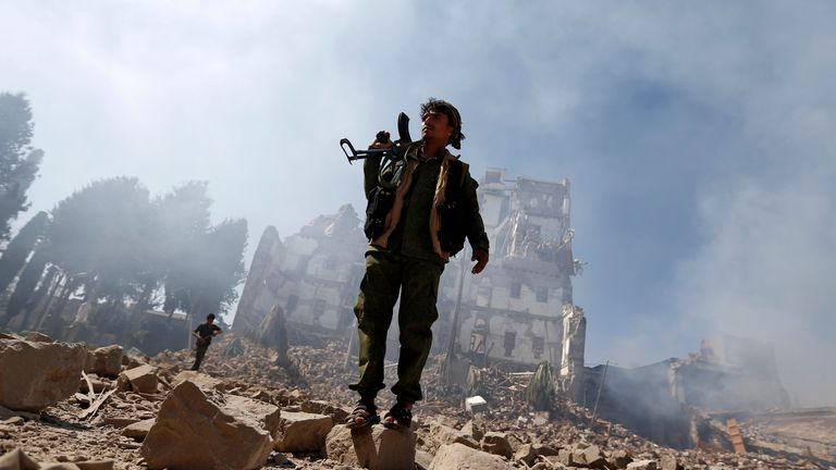 A Houthi rebel inspects damage caused after an airstrike reportedly carried out by the Saudi-led coalition