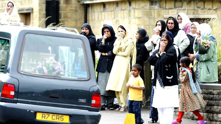 Mourners watch hearses carrying the Chishti family