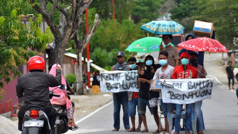 People hold signs asking for help after their homes were destroyed