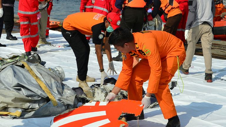 Rescue team members arrange the wreckage, showing part of the logo of Lion Air flight JT610