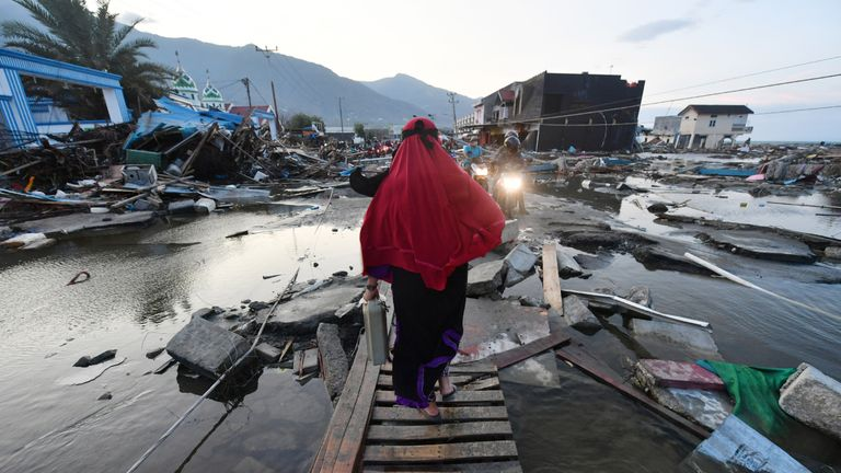 A woman walks through a devastated area in Palu, in Indonesia's Central Sulawesi