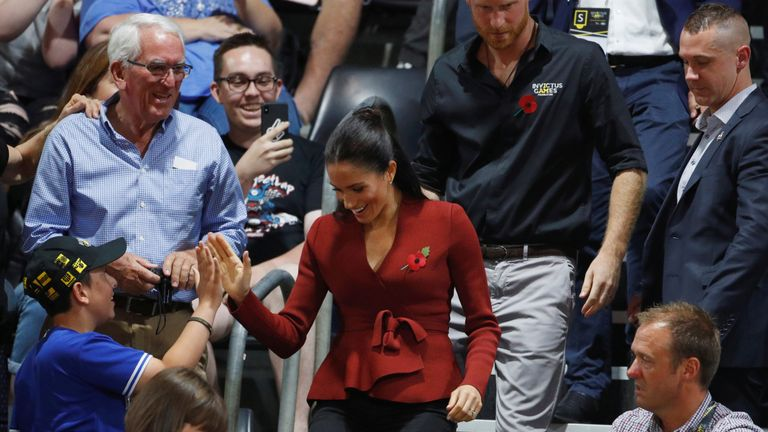Meghan, Duchess of Sussex, gives a spectator a high five as she walks to her seat with Britain's Prince Harry to watch the Invictus Games Sydney 2018 wheelchair basketball gold medal match at Quaycentre in Sydney, Australia October 27, 2018