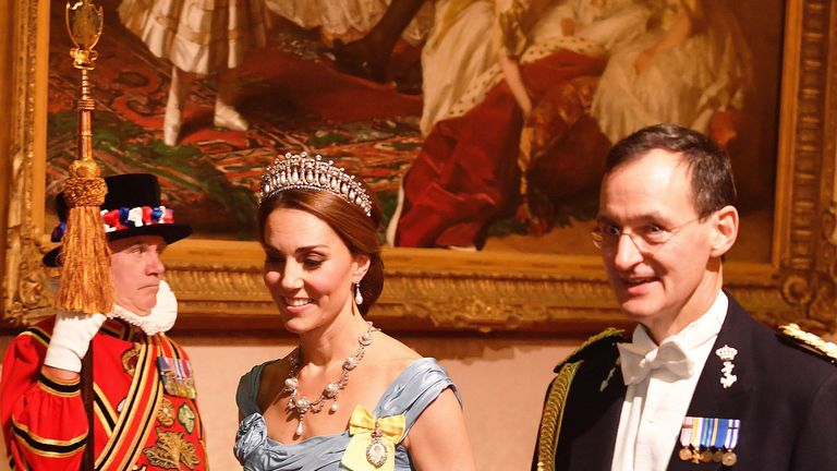 Catherine, Duchess of Cambridge, walks with Rear Admiral Ludger Brummelaar during the state banquet