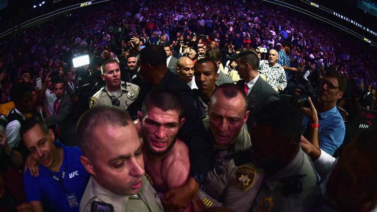 Khabib Nurmagomedov of Russia is escorted out of the arena after defeating Conor McGregor