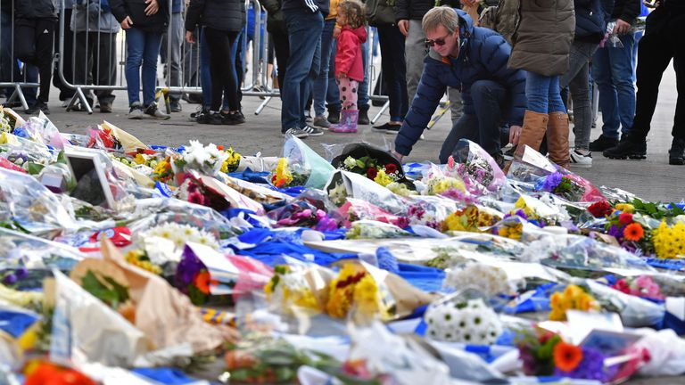 A man adds flowers to a growing pile of tributes outside Leicester City Football Club's King Power Stadium in Leicester, eastern England, on October 28, 2018