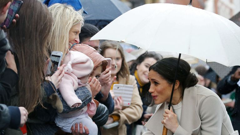 Prince Harry's fiancee, US actress Meghan Markle plays with a baby as she greet well-wishers after a visit to one of Belfast's most historic buildings, The Crown Liquor Saloon, a former Victorian gin palace, now run by the National Trust, on March 23, 2018, during the Royal Couple's first joint visit to Northern Ireland