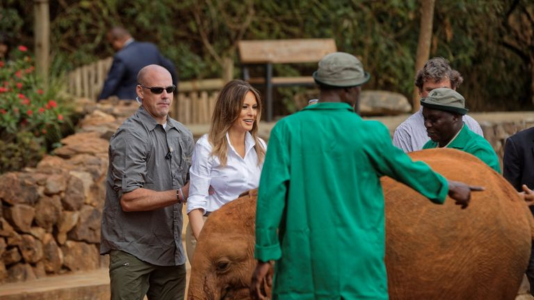 A Secret Service agent holds Melania Trump to protect her after being nudged by a baby elephant