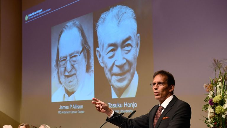 Secretary of the Nobel Committee for Physiology or Medicine, Thomas Perlmann stands next to a screen displaying portraits of James P Allison (L) and Tasuku Honjo