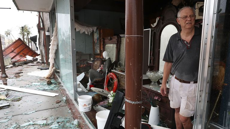 Mike Lindsey stands in his antique shop after the winds from hurricane Michael broke the windows in his shop on October 10, 2018 in Panama City