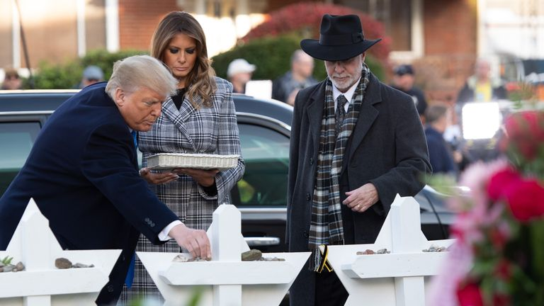 US President Donald Trump and First Lady Melania Trump, alongside Rabbi Jeffrey Myers, place stones and flowers on a memorial as they pay their respects at the Tree of Life Synagogue in Pittsburgh, Pennsylvania