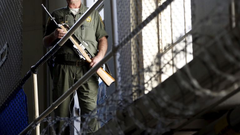 An armed guard patrols on the East Block for condemned prisoners during a media tour of California's Death Row at San Quentin State Prison in San Quentin, California December 29, 2015