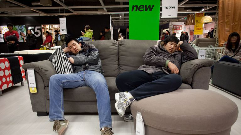 Two men sleep on a couch in a furniture store in Beijing on February 17, 2012