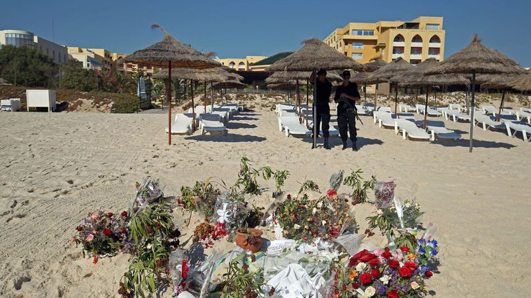 Flowers remain on the beach as police office patrol near the RIU Imperial Marhaba hotel in Sousse, Tunisia