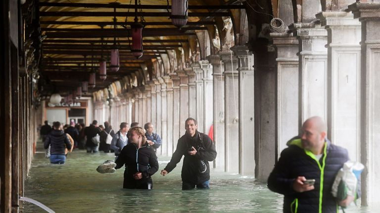 Tourists under arches next to the flooded St Mark's Square in Venice