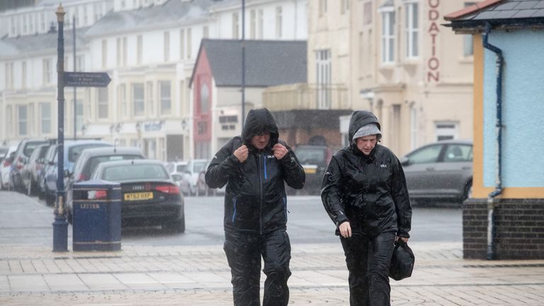 A couple walk along a windy seafront on Friday as Storm Callum brings high winds and rain.