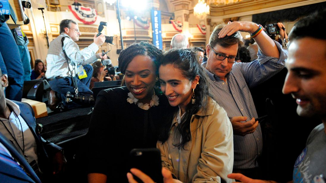 Congresswomen Ayanna Pressley poses for selfies with supporters in Massachusetts