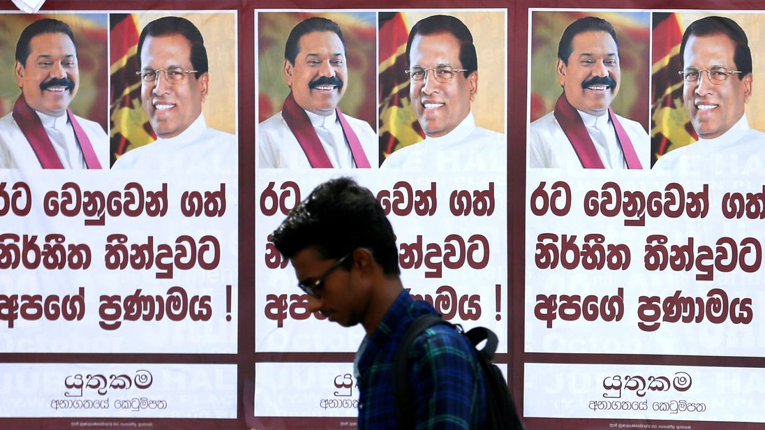 A man walks past a poster of Sri Lanka's newly appointed Prime Minister Mahinda Rajapaksa and President Maithripala Sirisen