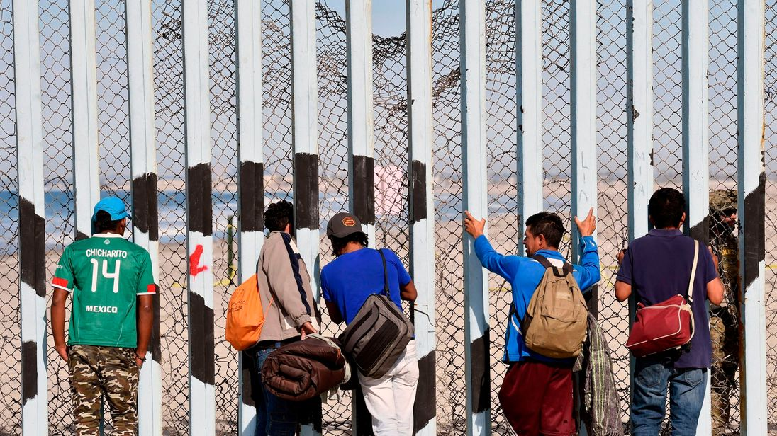 Migrants from the caravan heading from central America look at the US through the border fence