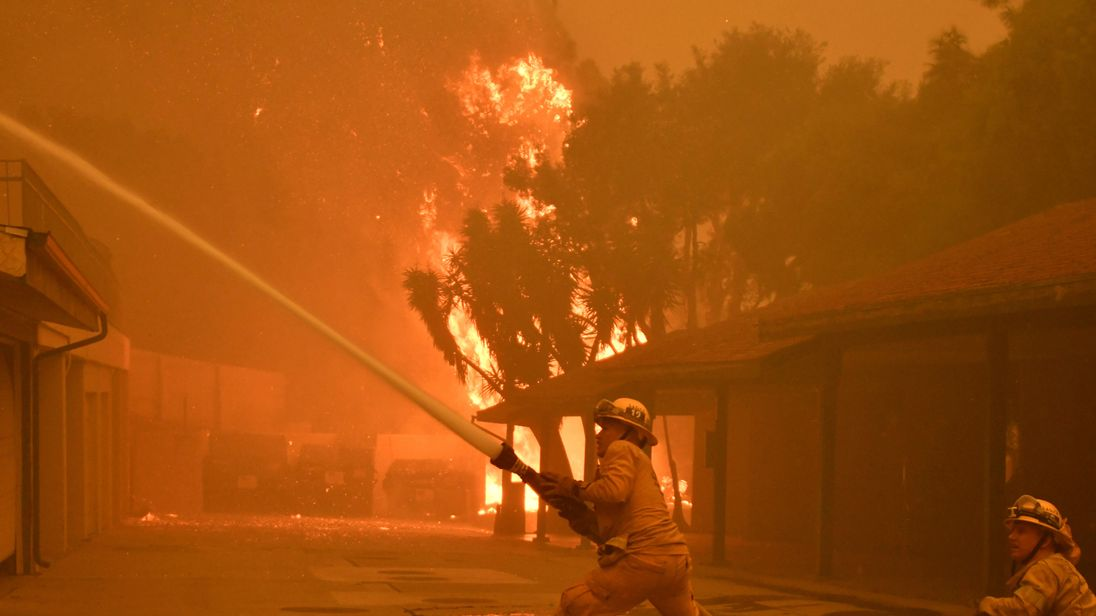 Firefighters hose down a condo unit during the Woolsey Fire in Malibu, California, U.S. November 9, 2018