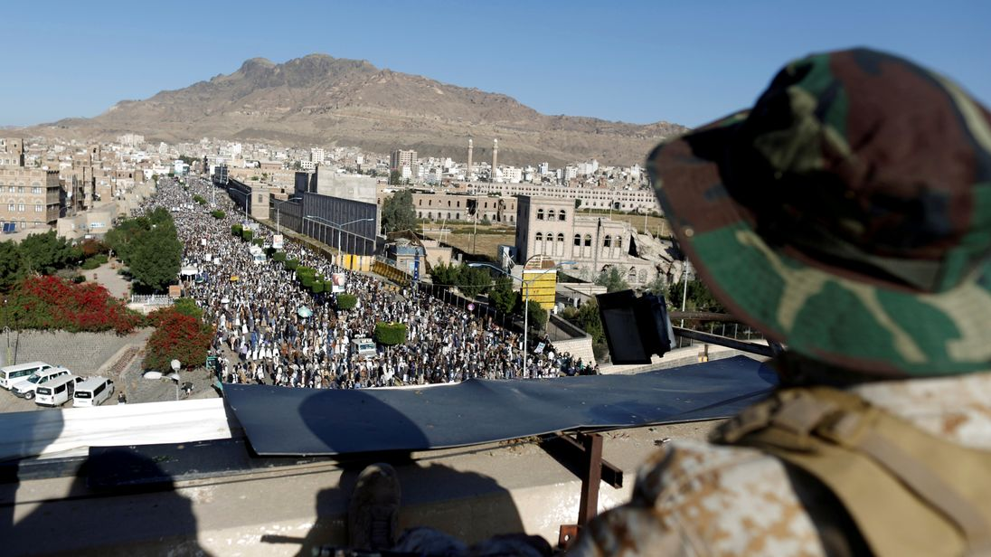 A Houthi militant sits guard on the roof of a building in Sanaa