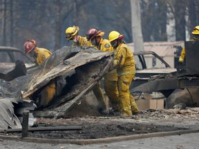 Firefighters comb through a house destroyed by the Camp Fire in Paradise, California